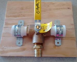 A closeup of the diverter valve, the hose barb, the PVC adapters, and the pipe straps